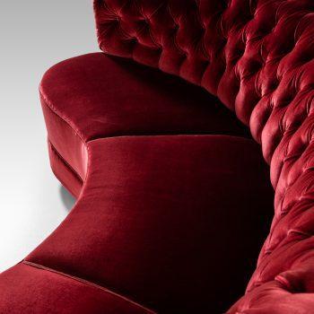 Large freestanding curved sofa in red velvet at Studio Schalling